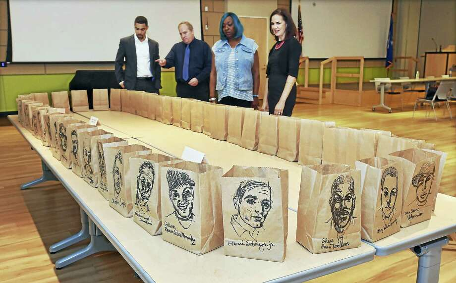 """David Heath, event organizer, second from left, talks about display by San Diego artist James Nocito, """"Orlando 49: Farolitos"""" a traveling memorial of the 49 men and women who were killed at the Pulse Nightclub in Orlando in 2016 following the panel discussion with law enforement and the LGBTQ communitiy at Gateway Community College in New Haven, Wednesday. Also picture from left to right, Erick Russell, an attorney at Pullman & Coley and chair of the LGBT section of the Connecticut Bar Association, Heath, Barbara Greene, of West Haven and Connecticut's U.S. attorney Deirdre M. Daly. Photo: Catherine Avalone / Hearst Connecticut Media    / Catherine Avalone/New Haven Register"""
