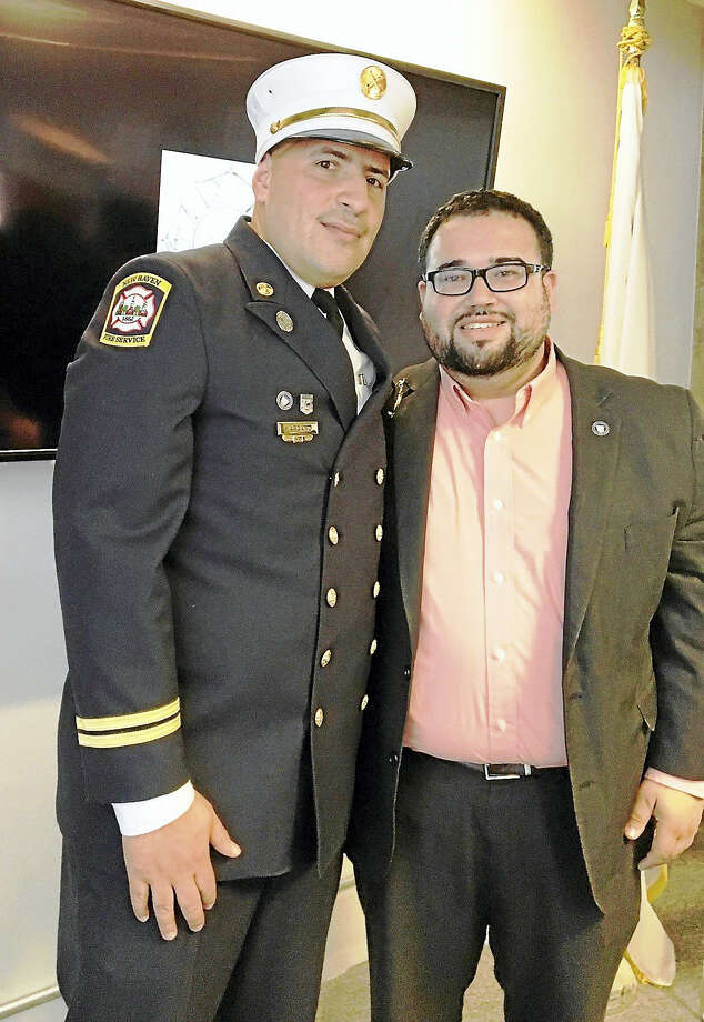 Orlando Marcano, left, was promoted to assistant fire chief of administration Monday. His badge was pinned by Alder David Reyes, D-5, at right. Photo: Mary O'Leary / Hearst Connecticut Media
