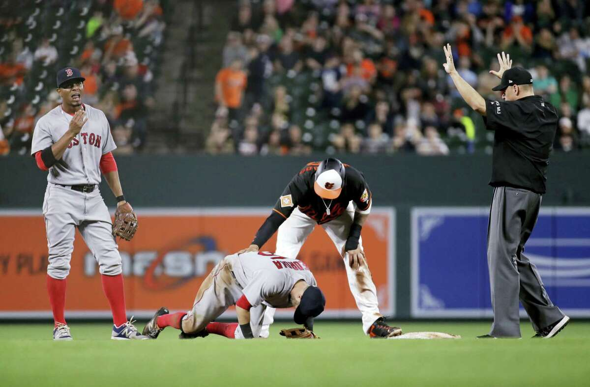 Red Sox second baseman Dustin Pedroia, second from left, struggles to stand after colliding with the Orioles' Manny Machado during the eighth inning on Friday.