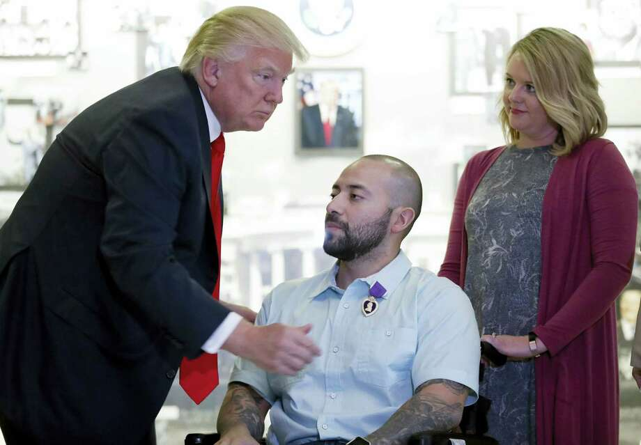 President Donald Trump awards a Purple Heart to U.S. Army Sgt. First Class Alvaro Barrientos, with his wife Tammy Barrientos standing right, at Walter Reed National Military Medical Center, Saturday, April 22, 2017, in Bethesda, Md. Photo: AP Photo/Alex Brandon    / Copyright 2017 The Associated Press. All rights reserved.