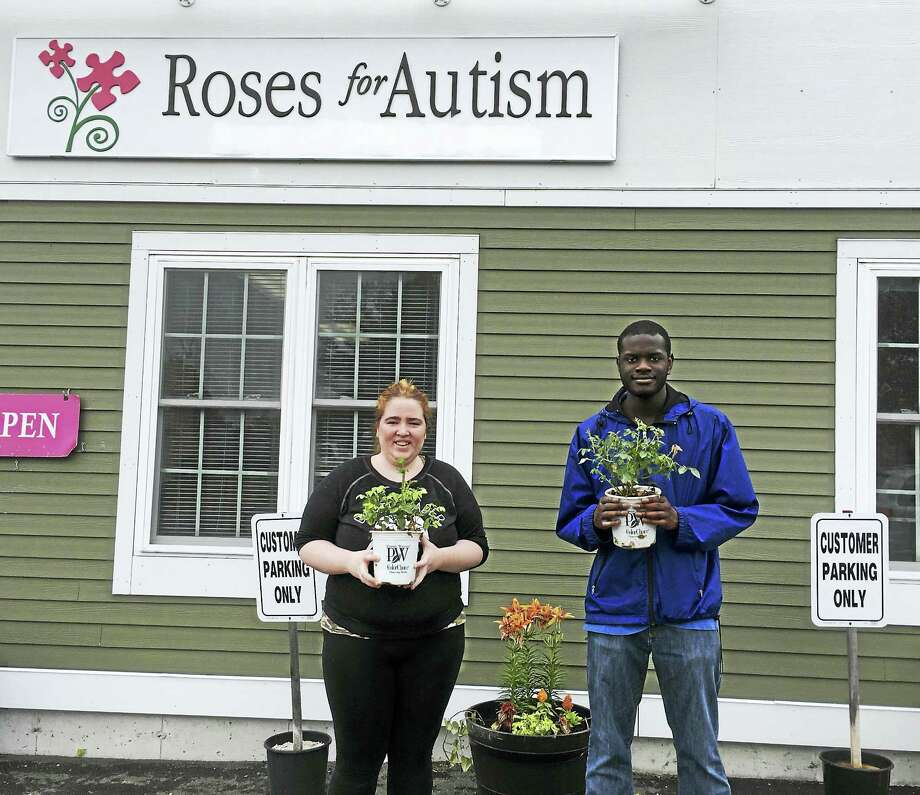 Roses for Autism interns, Katie and Justin, hold two of the 84 rose bushes donated by Prides Corner Farms after learning the farm's new sensory garden was destroyed by vandals. Roses for Autism has been flooded with donations since news of the damage spread. Photo: Roses For Autism / Submitted Photo
