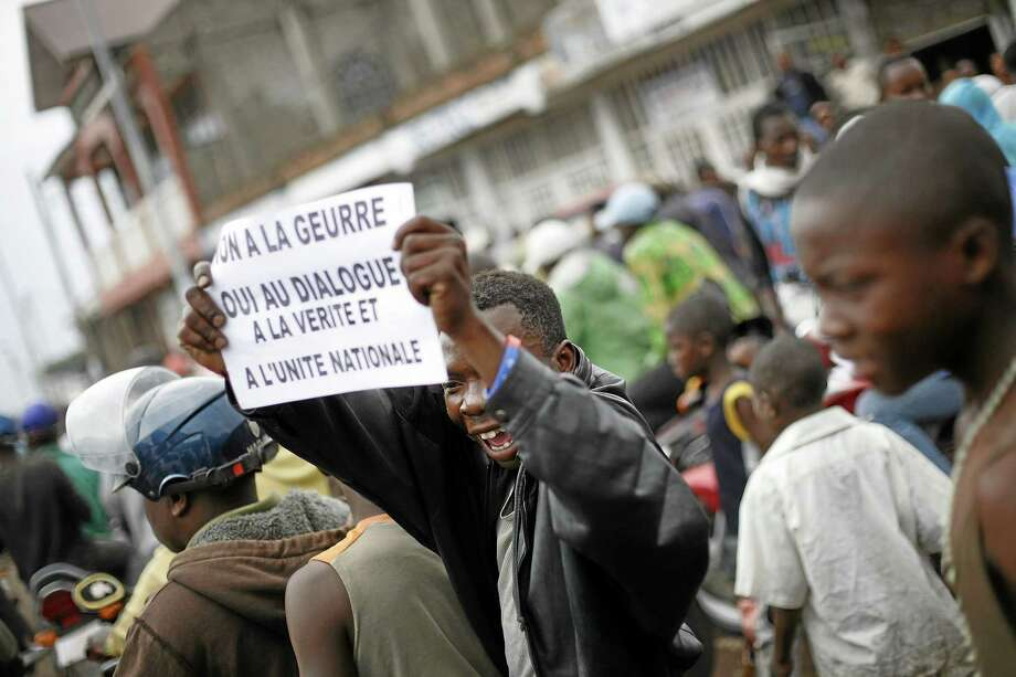 """A Goma resident holds up a banner in French reading, """"No to war, yes to dialogue, the truth and national unity"""" as he gathers with others for an anti-President Joseph Kabila demonstration supported by the M23 rebel movement in Goma, eastern Congo. Photo: Jerome Delay / The Associated Press    / AP"""