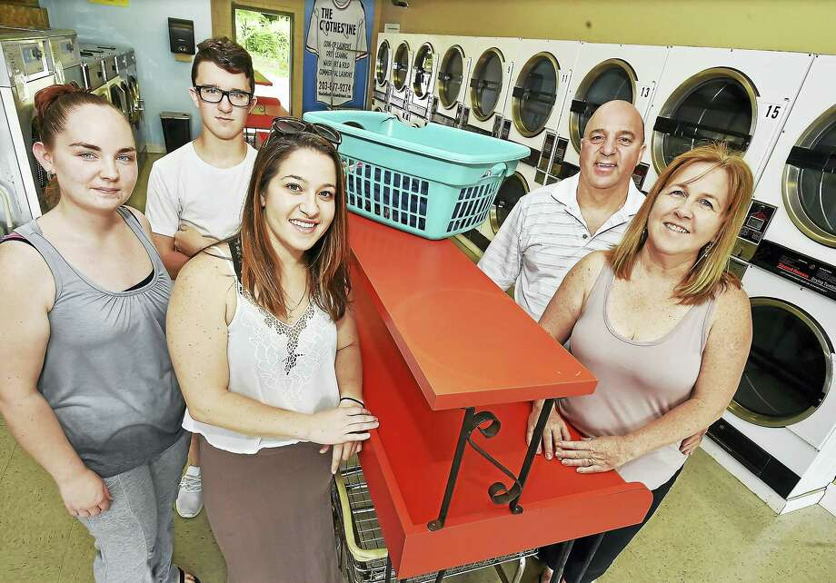 Jeff and Ellen Dorosh, of Naugatuck, owners of The Clothesline Laundromat and Dry Cleaners at 249 Naugatuck Ave., Milford with two of their four children, Elyse, 27, center, David, 16, and their employee Samantha Checca, at left. The Clothesline offers coin-op laundry, dry cleaning wash, dry and fold and commercial laundry seven days a week. Photo: Catherine Avalone / Hearst Connecticut Media   / Catherine Avalone/New Haven Register