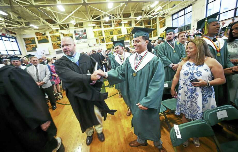 Assistant principal Adam Laput, left, shakes hands with Giuseppe Minichino as commencement begins at Notre Dame in West Haven. Photo: Arnold Gold — New Haven Register