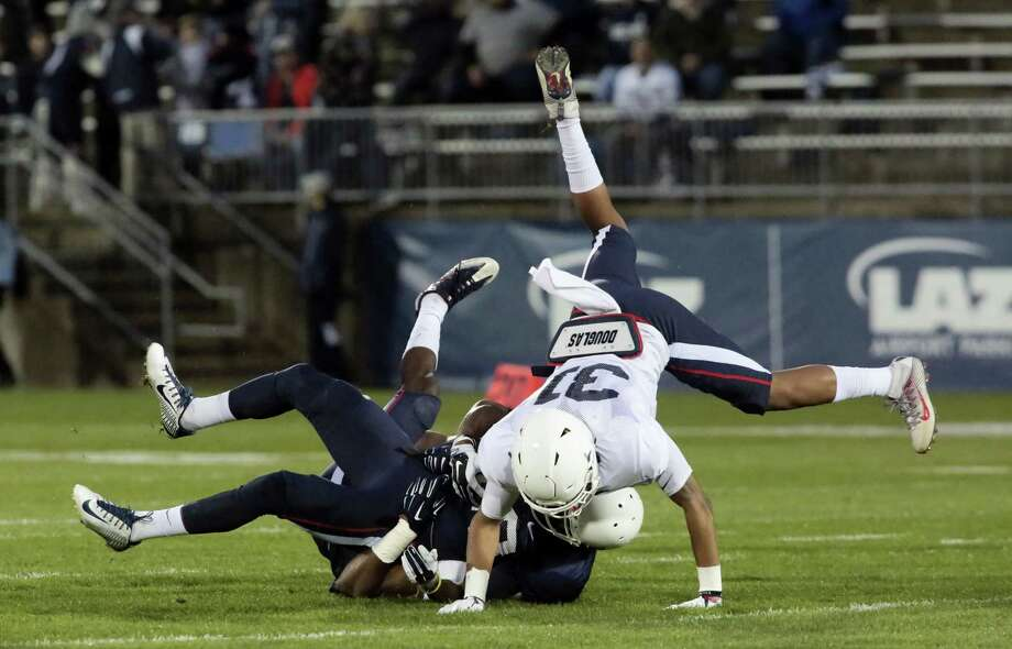 UConn receiver Keyion Dixon is tackled as defender John Robinson (31) goes over the top during the first half of Friday's spring game at Rentschler Field. Photo: Michael McAndrews — Hartford Courant Via AP    / Hartford Courant