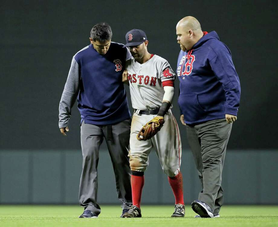 Red Sox second baseman Dustin Pedroia, center, is assisted off the field after being injured in the eighth inning Friday. Photo: Patrick Semansky — The Associated Press   / Copyright 2017 The Associated Press. All rights reserved.