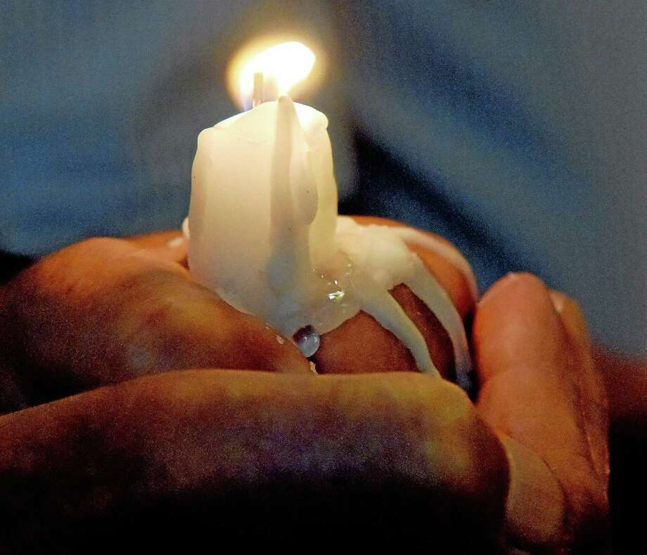 The hot wax melts in the hands of a congregant during a candle service in a local church. Photo: New Haven Register File Photo   / ©Peter Hvizdak /  New Haven Register