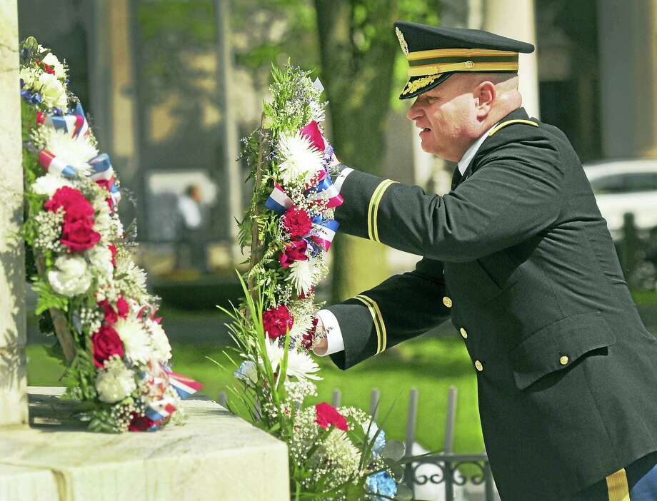 Lt. Col. James McClean of the Connecticut Army National Guard, a veteran of the Afghanistan war, lays a wreath by the War Memorial and flagpole on the New Haven Green in a previous Memorial Day ceremony. Photo: Peter Hvizdak — New Haven Register File Photo   / ?Peter Hvizdak /  New Haven Register