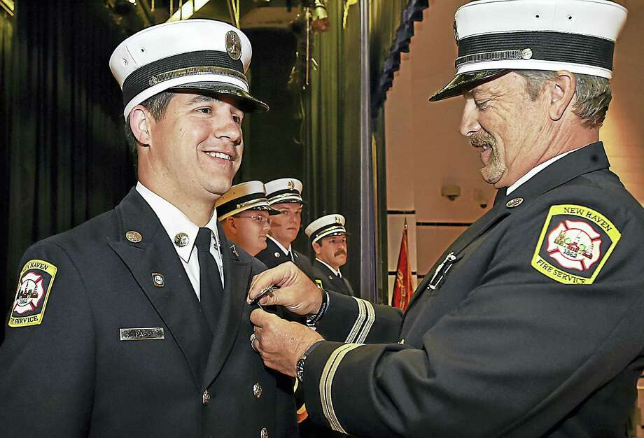 Fire Lt. Timothy N. Papp is promoted to captain Friday at James Hillhouse High School. His badge is being pinned on by retired Capt. Karl Luschenat. In the background, Lts. Justin D. Bialecki, Gregory W. Carroll and Christopher M. Brigham were also promoted to captain. Photo: Catherine Avalone — New Haven Register   / Catherine Avalone/New Haven Register