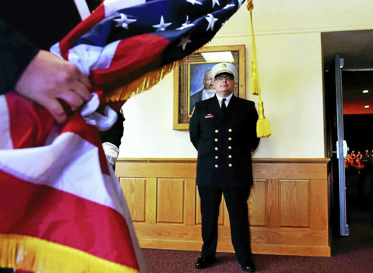 New East Haven Fire Chief Matthew Marcarelli waits for the start of the procession with the honor guard to escort him to his swearing-in ceremony Thursday in the auditorium of Joseph Melillo Middle School.