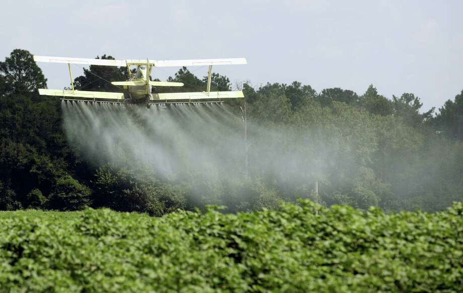 A crop duster sprays a field of crops just outside Headland, Ala. Dow Chemical is pushing the Trump administration to scrap the findings of federal scientists who point to a family of widely used pesticides as harmful to about 1,800 critically threatened or endangered species. Photo: AP Photo — Dave Martin, File   / AP2009