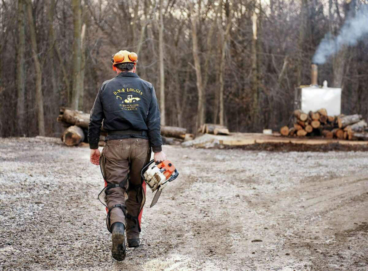 Darwin Woods carries a chainsaw to cut wood for the wood burning stove he uses to heat both water and his home in Clark, Mo.