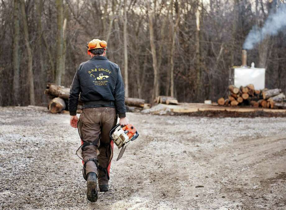 Darwin Woods carries a chainsaw to cut wood for the wood burning stove he uses to heat both water and his home in Clark, Mo. Photo: L.G. Patterson — THE ASSOCIATED PRESS FILE PHOTO   / FR23535 AP