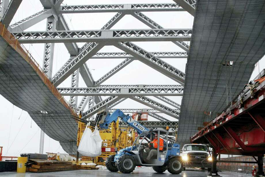 A worker lifts materials as construction continues on the new roadway deck of the Bayonne Bridge in Bayonne, N.J. Photo: Mel Evans — THE ASSOCIATED PRESS FILE PHOTO   / Copyright 2016 The Associated Press. All rights reserved.