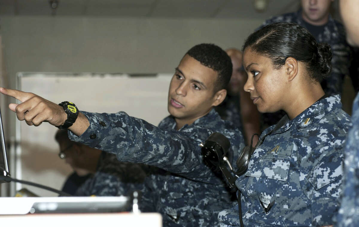 In this May 16, 2012 photo, released by the U.S. Navy, Petty Officer 3rd Class DonPaul Mitchell, left, assigned to the guided-missile submarine USS Georgia, instructs Ensign Tabitha Strobel, Georgia's main propulsion assistant, in a trainer at Naval Submarine Base Kings Bay in Georgia. With women now serving on submarines, future subs are being built to specifically accommodate gender differences including height, reach and strength. The first vessel built with some of the new features is expected to be delivered in 2021.