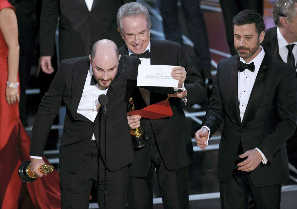 """Jordan Horowitz, producer of """"La La Land,"""" shows the envelope revealing """"Moonlight"""" as the true winner of best picture at the Oscars on Sunday at the Dolby Theatre in Los Angeles. Presenter Warren Beatty and host Jimmy Kimmel look on from right."""