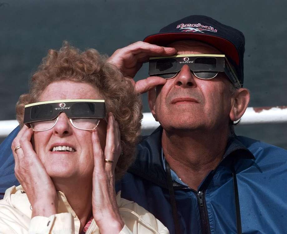 People watch a solar eclipse from the deck of a specially chartered ferry in the English Channel, 11th August 1999. (Photo by Colin Davey/Getty Images) Photo: Colin Davey/Getty Images, Courtesy Of Homeowner/Airbnb