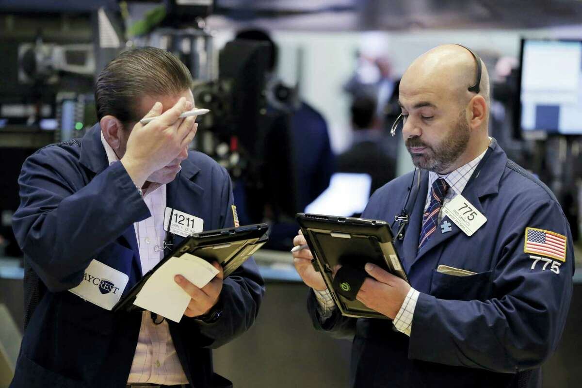 Traders Tommy Kalikas, left, and Fred Demarco work on the floor of the New York Stock Exchange Friday.