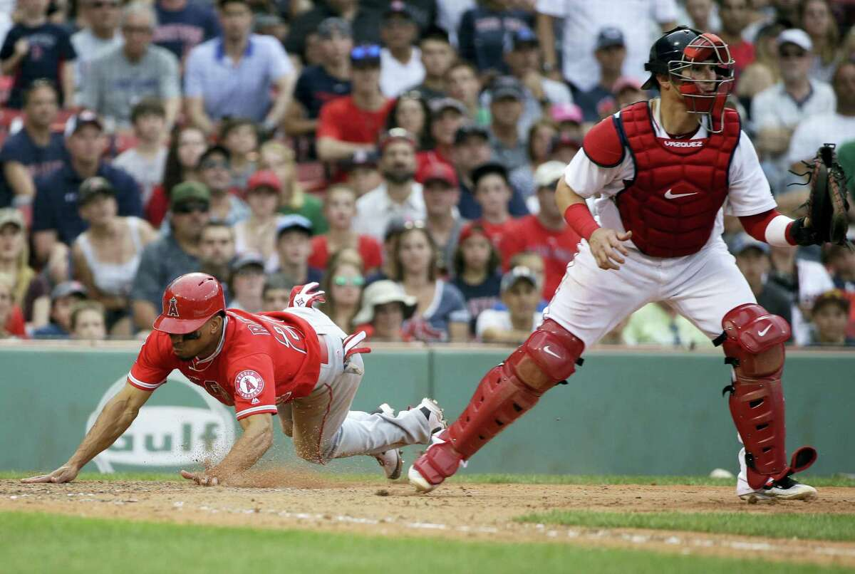 The Angels' Ben Revere, left, scores as Red Sox catcher Christian Vazquez, right, waits for the ball in the eighth inning Sunday.