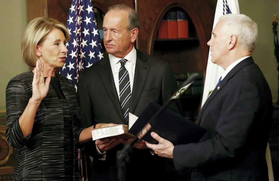 Vice President Mike Pence swears in Education Secretary Betsy DeVos in the Eisenhower Executive Office Building in the White House complex in Washington on Feb. 7, 2016 as DeVos' husband Dick DeVos watches. Photo: AP Photo — Pablo Martinez Monsivais   / Copyright 2017 The Associated Press. All rights reserved.