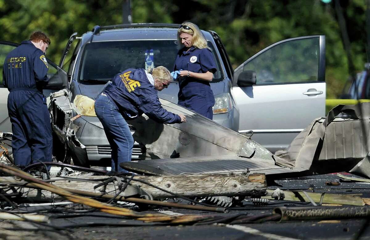 In this file photo, investigators look at the remains of a small plane along Main Street in East Hartford, Conn. Police say the student pilot of the small plane, which crashed on Oct. 11, near the Connecticut headquarters of a military jet engine manufacturer, fought with his instructor and probably crashed deliberately. East Hartford police reports disclosed Tuesday support media stories from months ago.
