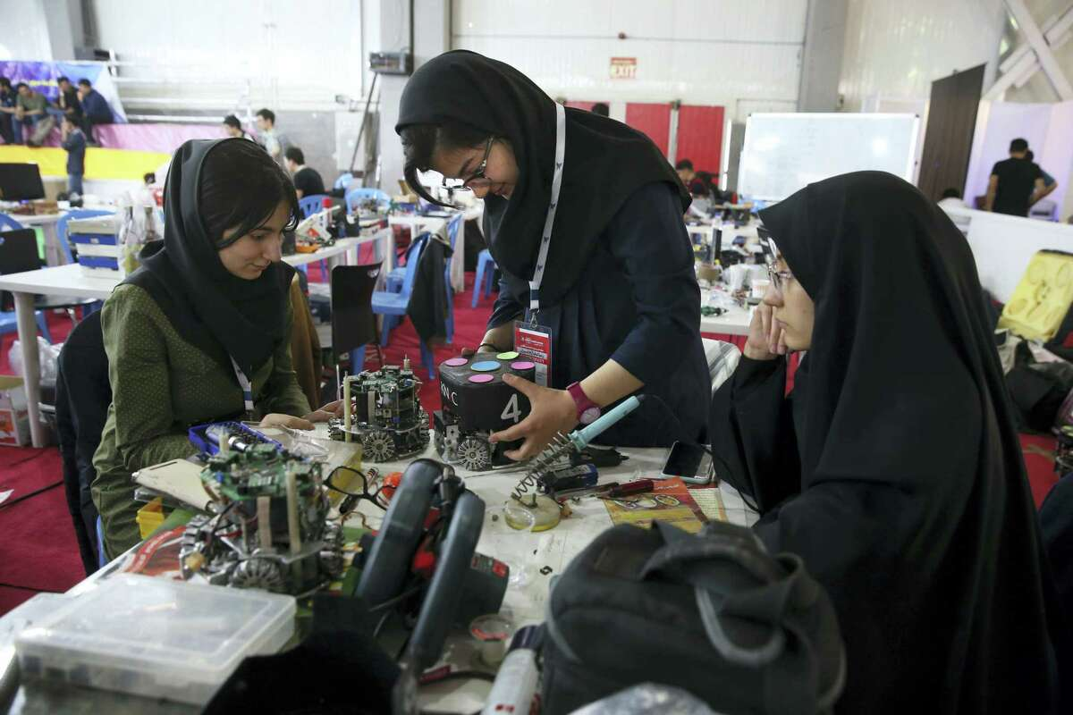In this file photo, Iranian students prepare their robots during the international robotics competition, RoboCup Iran Open 2016, in Tehran, Iran. Universities in the U.S. say President Donald Trump's revised travel ban would block hundreds of graduate students who play key roles in research. Twenty-five of America's largest universities told The Associated Press they've sent acceptance letters to more than 500 students from the six banned countries for next fall, mostly from Iran, who are known for their strength in engineering and sciences.