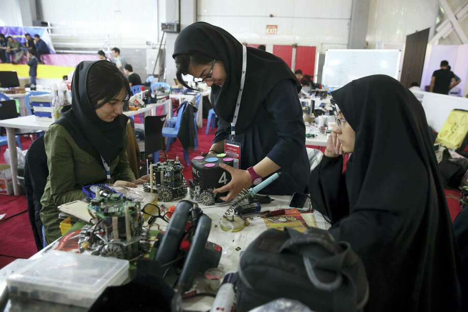 In this file photo, Iranian students prepare their robots during the international robotics competition, RoboCup Iran Open 2016, in Tehran, Iran. Universities in the U.S. say President Donald Trump's revised travel ban would block hundreds of graduate students who play key roles in research. Twenty-five of America's largest universities told The Associated Press they've sent acceptance letters to more than 500 students from the six banned countries for next fall, mostly from Iran, who are known for their strength in engineering and sciences. Photo: Vahid Salemi — The Associated Press   / Copyright 2017 The Associated Press. All rights reserved.