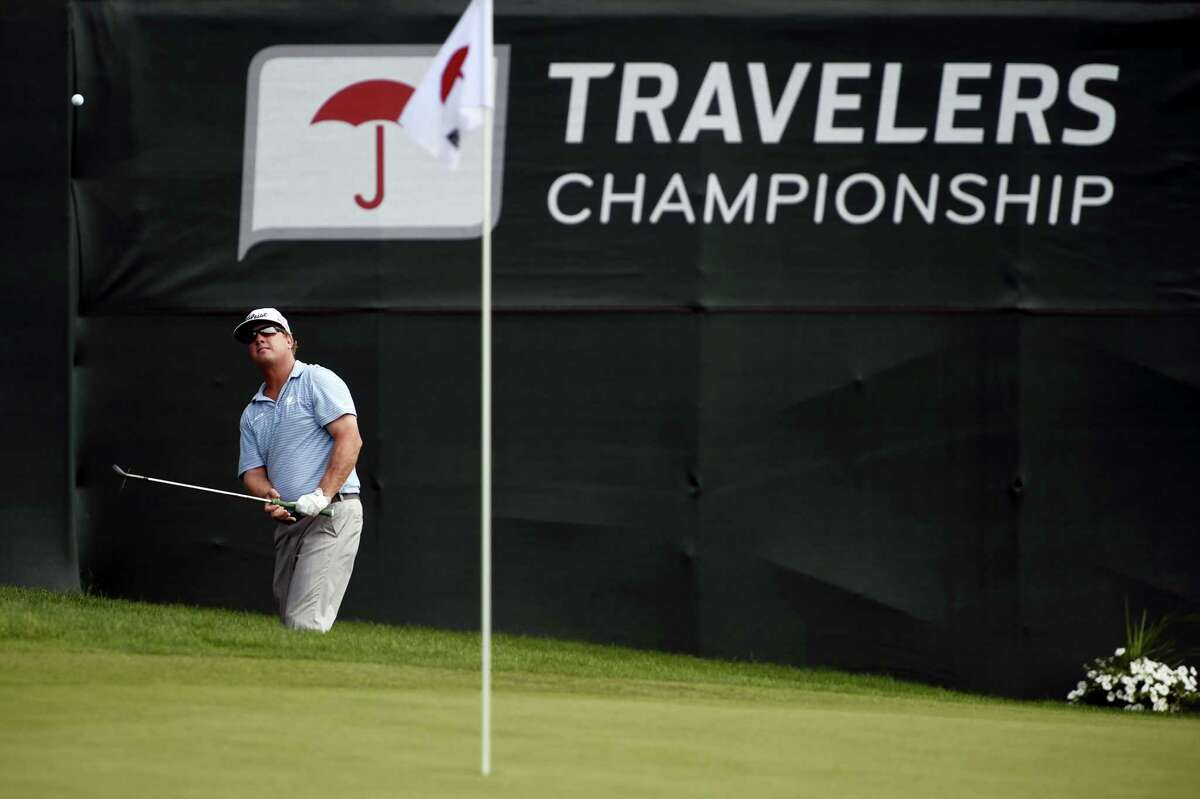 Charley Hoffman hits from the rough around the 17th green during the third round of the Travelers Championship on Saturday.