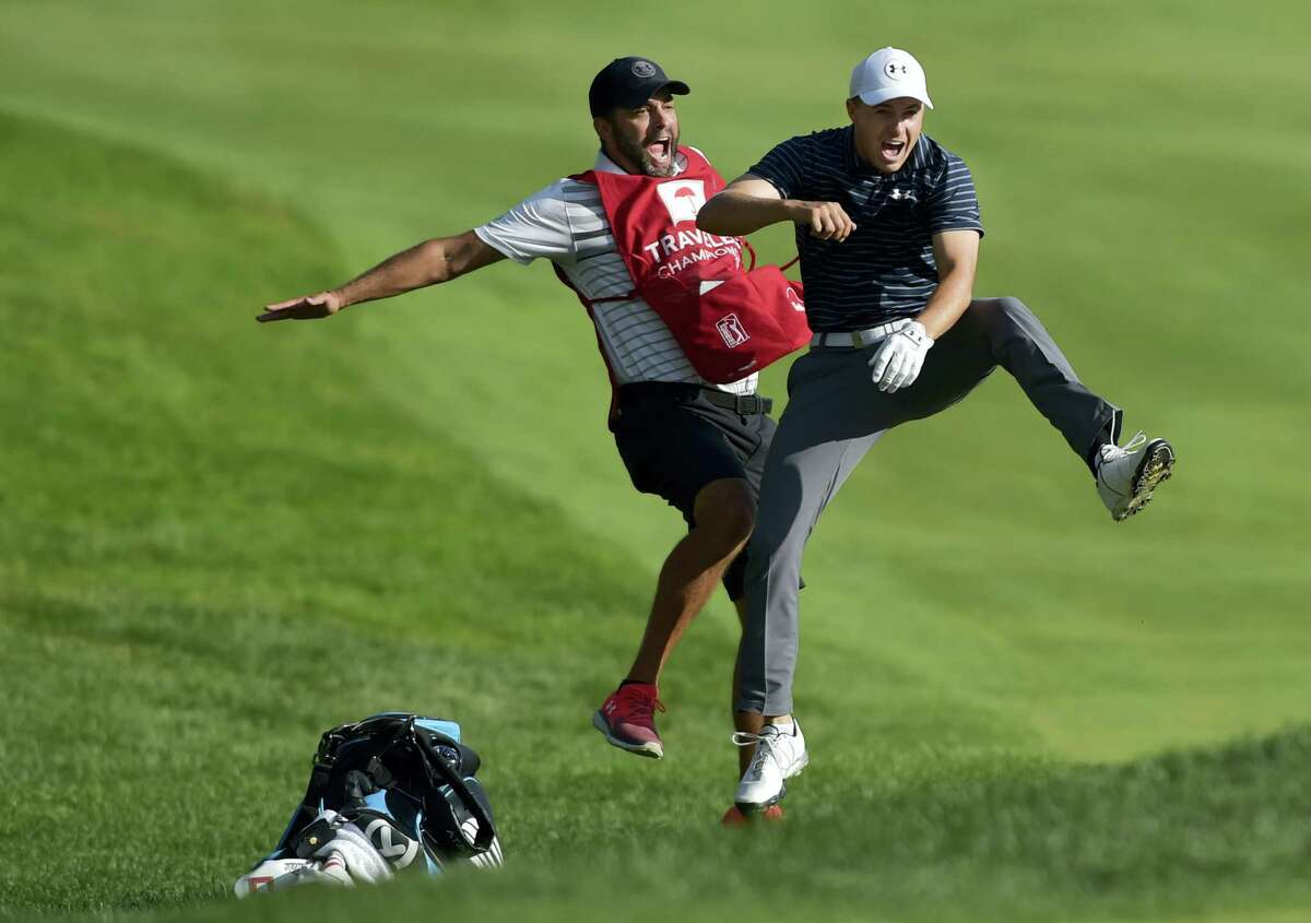 Jordan Spieth, right, celebrates with caddie Michael Greller after Spieth holed a bunker shot on the first playoff hole to win the Travelers Championship Sunday in Cromwell.