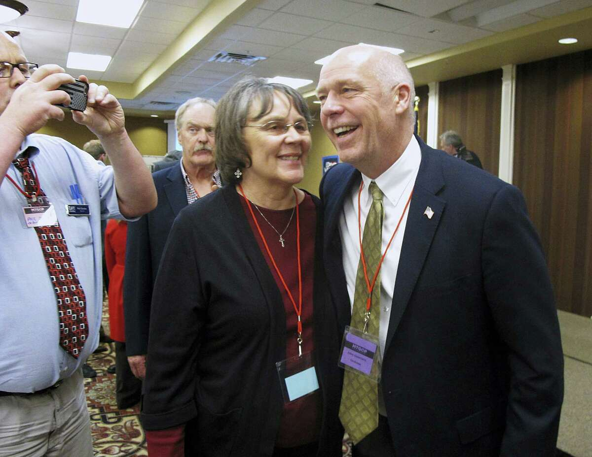 In this March 6, 2017 photo, Greg Gianforte, right, receives congratulations from a supporter in Helena, Mont. Montana voters are heading to the polls on May 25, 2017 to decide a nationally watched congressional election amid uncertainty in Washington over President Donald Trump's agenda and his handling of the country's affairs.