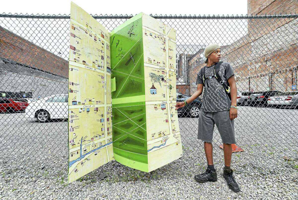 New Light High School senior Tyriq Banks, 17, positions a folding series of panels depicting the New Haven Green as a public art installation on Chapel Street in New Haven on Friday. Banks worked on the design and painting of the panels.