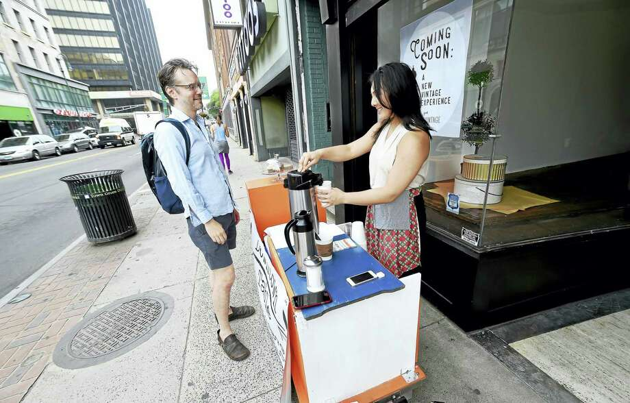 Jonathan Blessing, left, gets a cup of coffee from Katherine McComic at her mobile coffee cart, Downtown Table, on Chapel Street in New Haven on Friday. Photo: Arnold Gold / Hearst Connecticut Media
