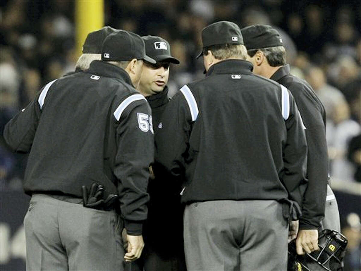 This Oct. 19, 2010 photo shows umpires huddling after an apparent home run by New York Yankees' Lance Berkman in the second inning of Game 4 of baseball's American League Championship Series against the Texas Rangers in New York. Major League Baseball umpires could start explaining replay decisions to the players and fans — the way NFL referees do — later this season if the sides can reach agreement. Under one possible scenario, the crew chief could wear a microphone beginning at the All-Star Game.