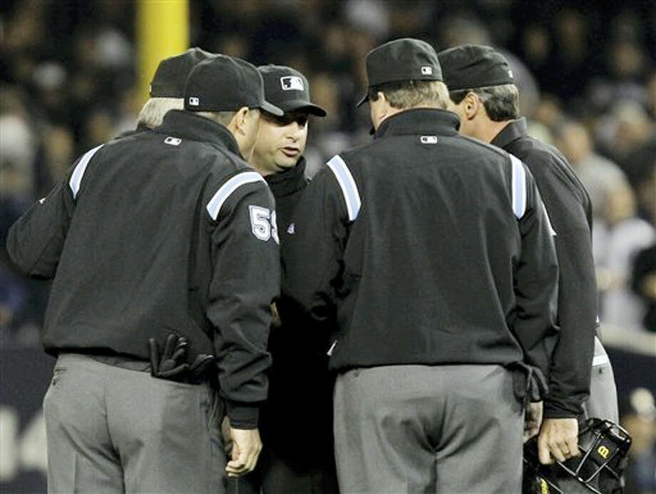 This Oct. 19, 2010 photo shows umpires huddling after an apparent home run by New York Yankees' Lance Berkman in the second inning of Game 4 of baseball's American League Championship Series against the Texas Rangers in New York. Major League Baseball umpires could start explaining replay decisions to the players and fans — the way NFL referees do — later this season if the sides can reach agreement. Under one possible scenario, the crew chief could wear a microphone beginning at the All-Star Game. Photo: AP Photo — Kathy Willens, File   / AP2010