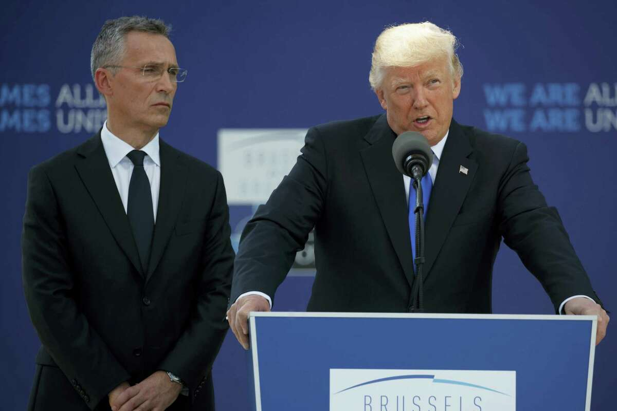 NATO Secretary General Jens Stoltenberg listens as President Donald Trump speaks during a ceremony to unveil artifacts from the World Trade Center and Berlin Wall for the new NATO headquarters, May 25, 2017, in Brussels.