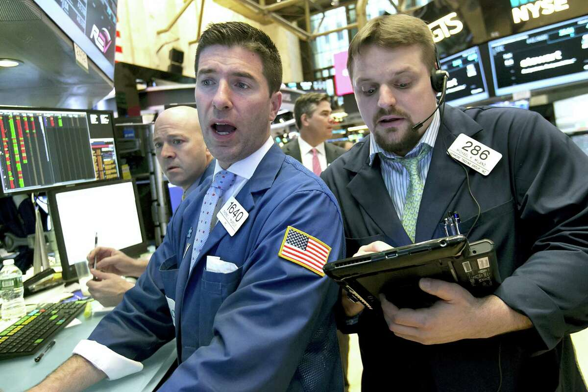 Specialist Thomas McArdle, center, and trader Michael Milano, right, work on the floor of the New York Stock Exchange, Wednesday. Stocks are opening mostly lower on Wall Street led by declines in utilities and real estate companies.