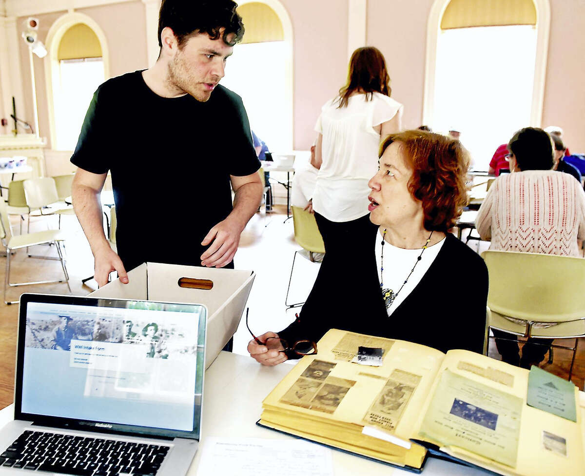 """Matt Bonito of the the Connecticut State Library's """"Remembering World War One — Sharing History/Preserving Memories"""" project, left, speaks with Gail Curran of New Haven during a Digitization Day event at the New Haven Museum in New Haven."""