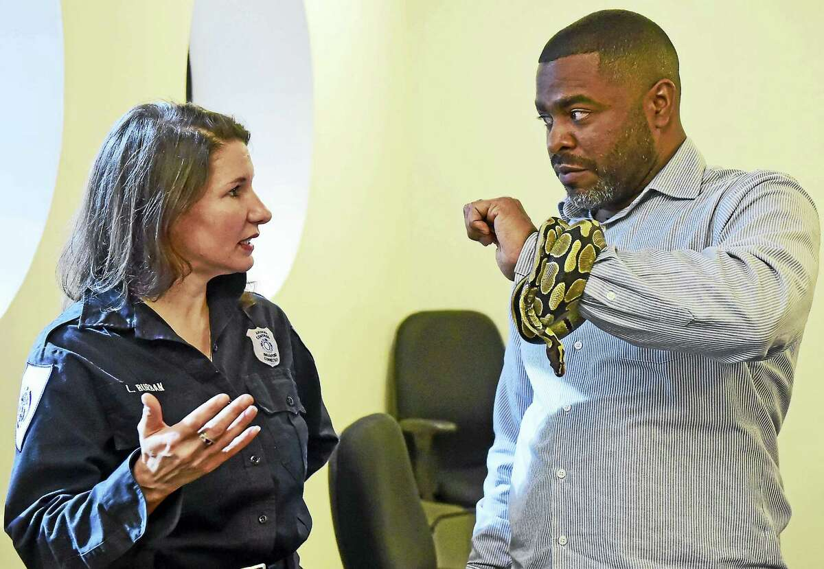 Laura Burban, director of the Daniel Cosgrove Animal Shelter of Branford, left, and Shahid Abdul-Karim of the New Haven Register with a ball python as they discuss the importance of pet adoption.