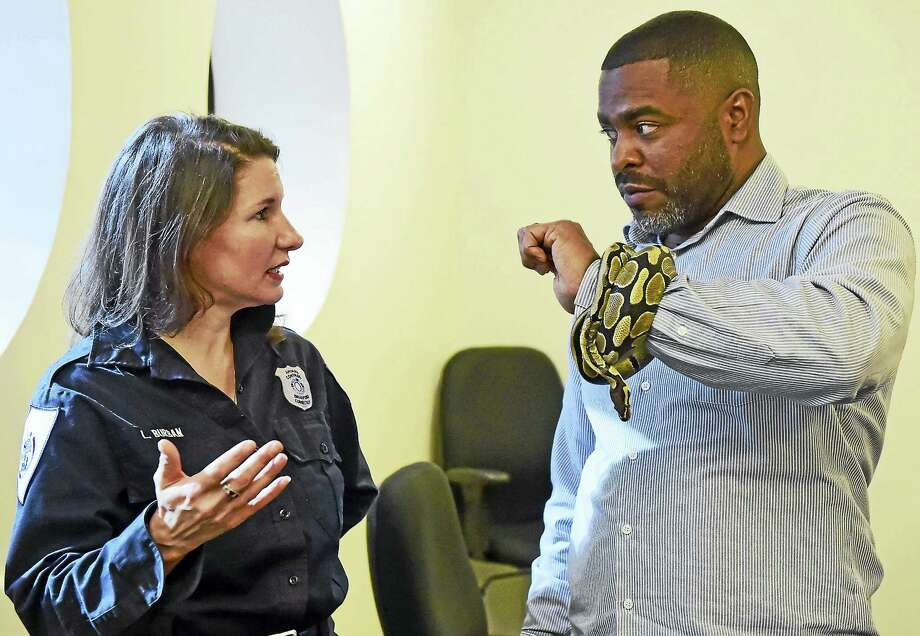 Laura Burban, director of the Daniel Cosgrove Animal Shelter of Branford, left,  and Shahid Abdul-Karim of the New Haven Register with a ball python as they discuss the importance of pet adoption. Photo: Peter Hvizdak — New Haven Register   / ©2017 Peter Hvizdak