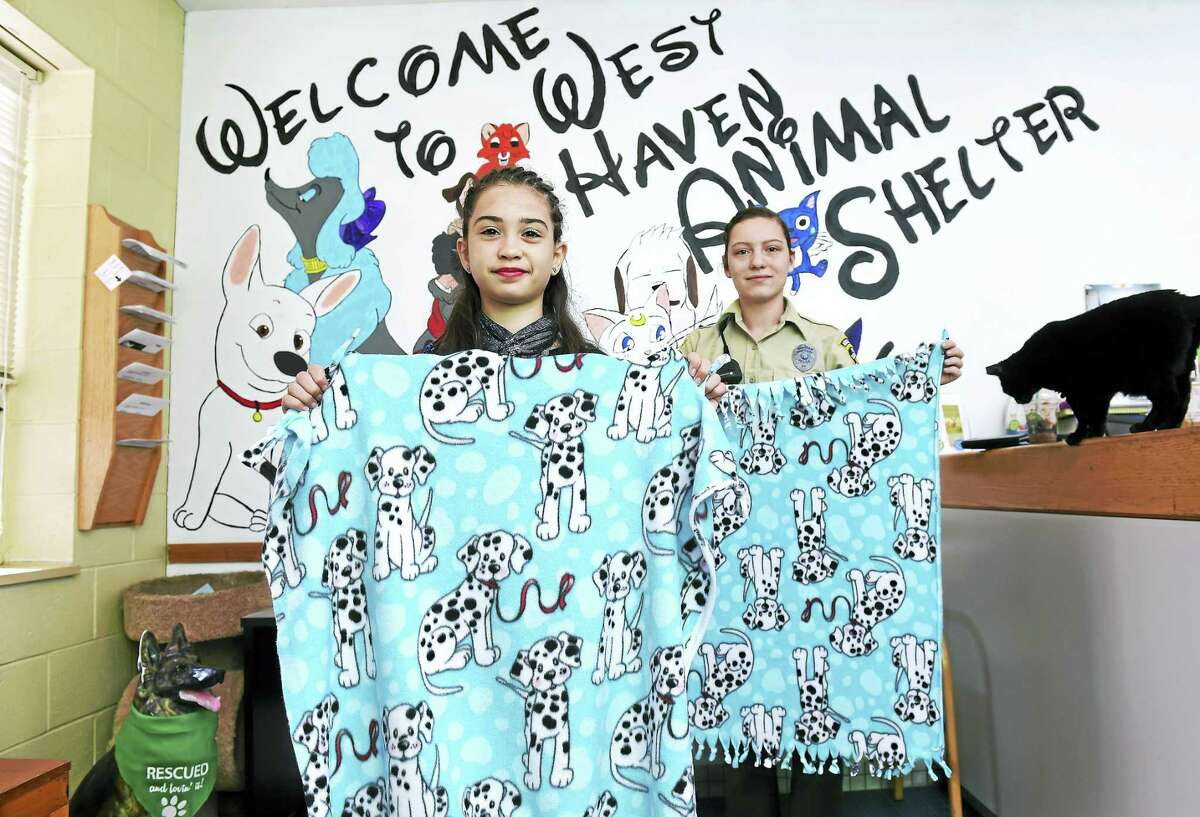 Lily Sutton (center), 11, of New Haven is photographed with Animal Control Officer Shannon Rose and a few of the blankets Sutton is donating to the West Haven Animal Shelter for the dogs and cats. The blankets were made by guests at Sutton's birthday party two weeks ago. At right is Shadow, a resident cat at the shelter.