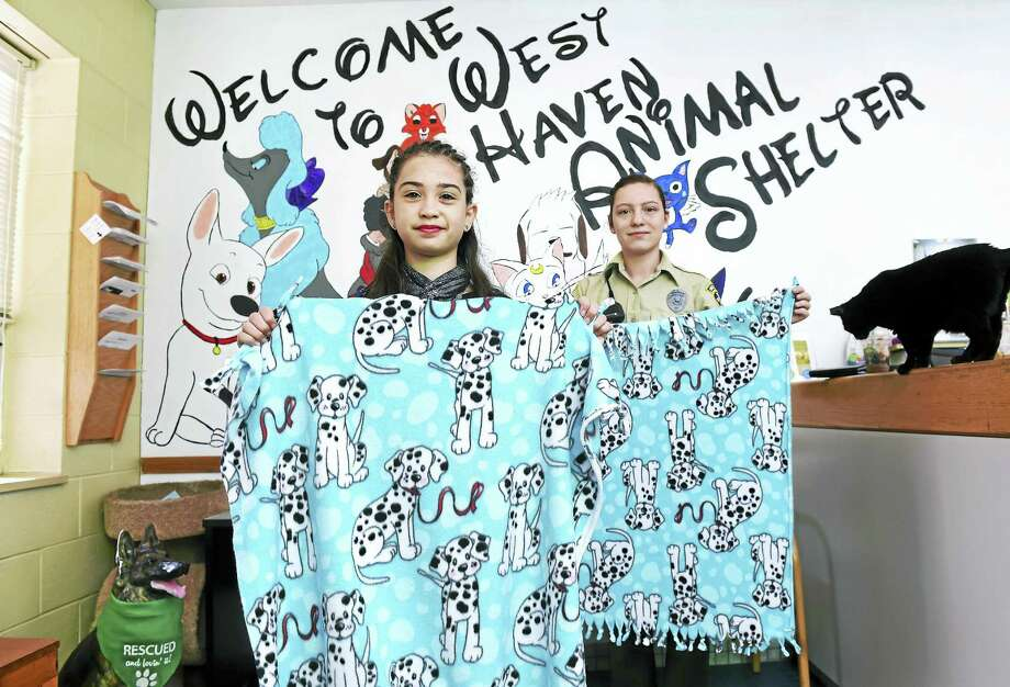 Lily Sutton (center), 11, of New Haven is photographed with Animal Control Officer Shannon Rose and a few of the blankets Sutton is donating to the West Haven Animal Shelter for the dogs and cats.  The blankets were made by guests at Sutton's birthday party two weeks ago. At right is Shadow, a resident cat at the shelter. Photo: Arnold Gold — New Haven Register
