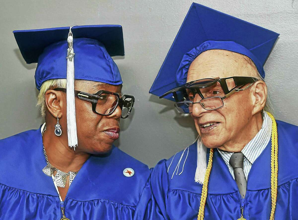 """Charlene Jones-Thomas and Sal Durso chat as members of the class of 2017 gather before Gateway Community College commencement Thursday in Wallingford. Durso, 86, received an associate degree in general studies, and is a former trapeze artist with Ringling Brothers and a professional clown. Durso enrolled in 1994 at the Long Wharf Campus. """"My time at Gateway was nothing less than wonderful; from the professors to the students and the curriculum. I'm glad I finally achieved what I set out to do. Now who knows where I'll go next, I have a lot of different ideas,"""" said Durso."""