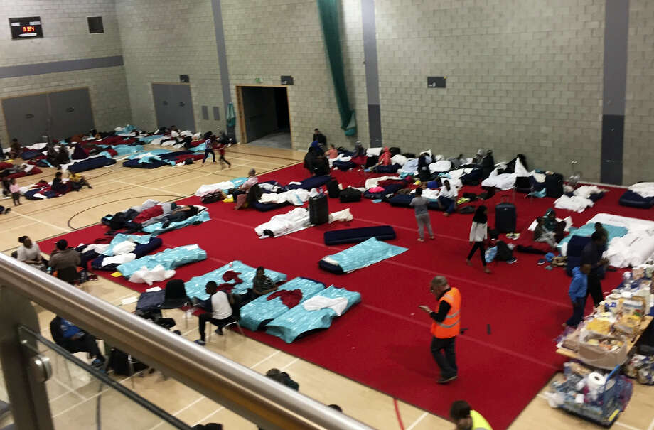 People gather in a leisure centre in Swiss Cottage, north London, Saturday June 24, 2017, after the local council evacuated some 650 homes overnight. Camden Borough Council said in a statement Saturday that it housed many of the residents at two temporary shelters while many others were provided hotel rooms, after inspectors found fire safety issues in housing towers, following the inferno in a west London apartment block that killed 79. Photo: AP Photo    / AP