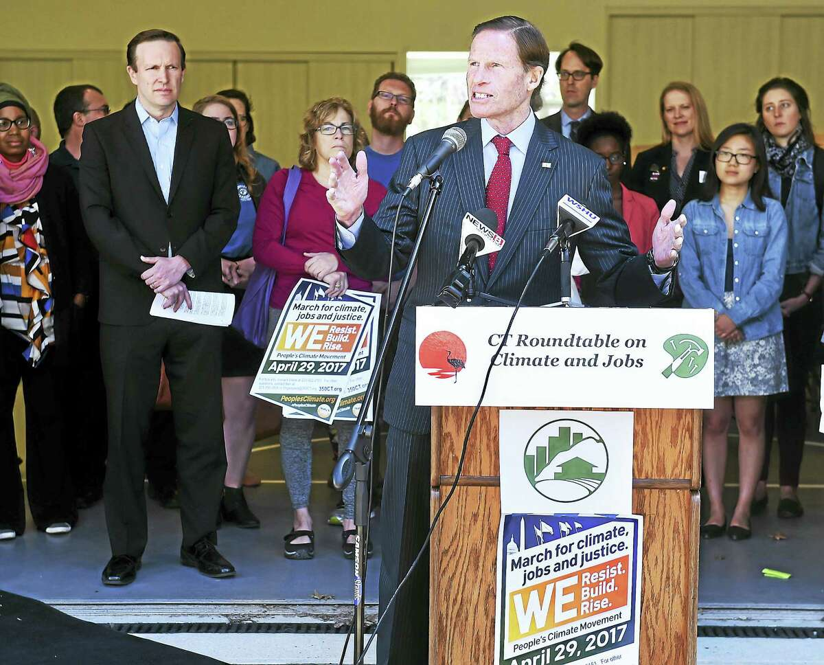 U.S. Sen. Chris Murphy, left, listens to Sen. Richard Blumenthal speak at a climate change press conference Tuesday at Common Ground High School in New Haven.