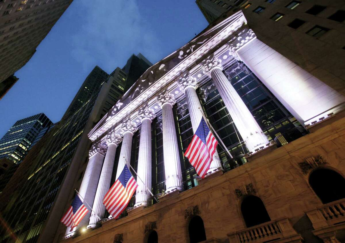 FILE - In this Oct. 8, 2014, file photo, American flags fly in front of the New York Stock Exchange. World stocks fell Tuesday, April 18, 2017, amid concerns about the security situation on the Korean Peninsula, France's upcoming presidential election, and Britain's surprise decision to hold a general election.