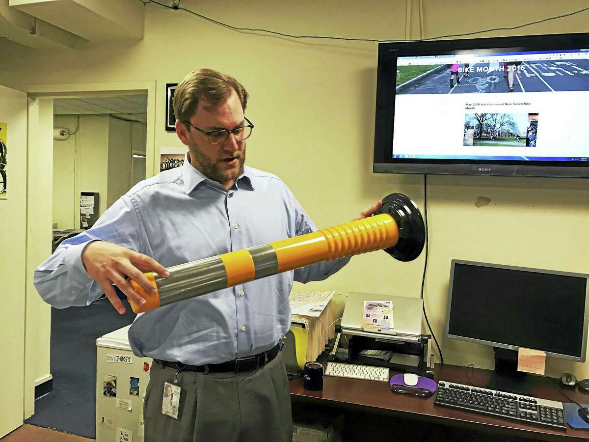"""City Transportation Director Douglas Hausladen holds a delineator, or """"rubber ducky,"""" which the city has started installing around city-owned streets this month."""