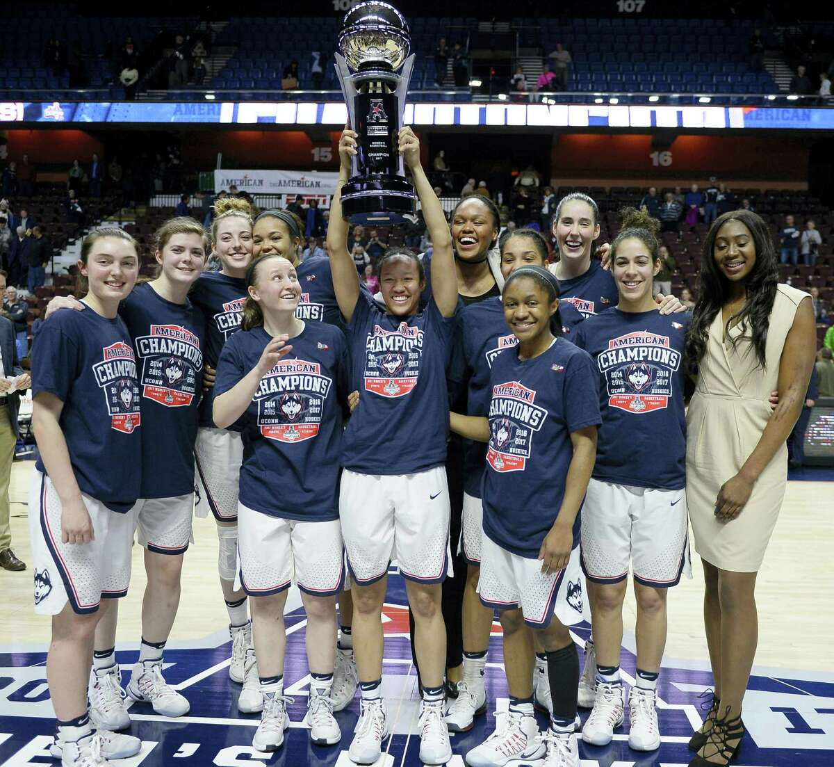 The Connecticut women's basketball team pose with the American Athletic Conference championship trophy after defeating South Florida in an NCAA college basketball game tournament final at Mohegan Sun Arena, March 6 in Uncasville, Conn.