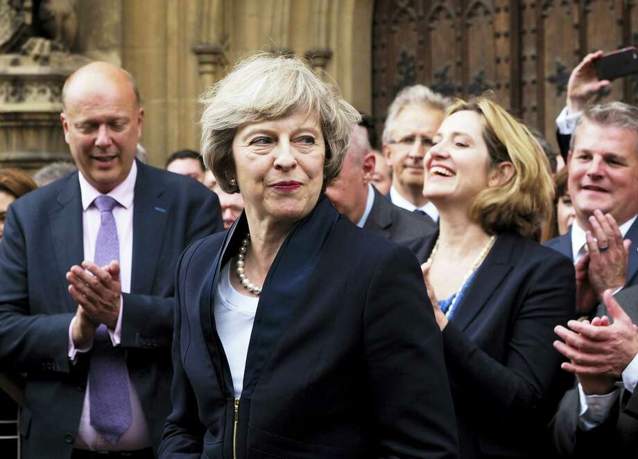 Max Nash — THE ASSOCIATED PRESS FILE PHOTO  Britain's Theresa May is applauded by Conservative Party members of parliament outside the Houses of Parliament in London July 11, 2016. Photo: AP / AP