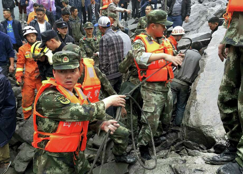 Emergency personnel work at the site of a massive landslide in Xinmo village in Maoxian County in southwestern China's Sichuan Province, Saturday, June 24, 2017. Dozens of people are feared buried by a landslide that unleashed huge rocks and a mass of earth that crashed into their homes in southwestern China early Saturday, a county government said. Photo: Chinatopix Via AP   / Chinatopix