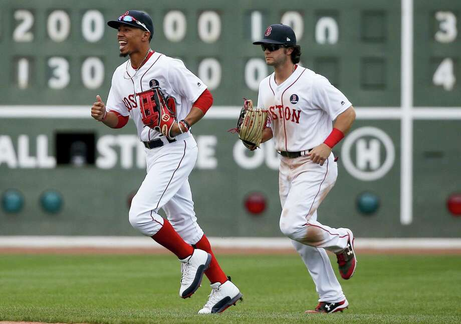Red Sox outfielders Mookie Betts, left, and Andrew Benintendi run past the scoreboard after Monday's win over the Rays. Photo: Michael Dwyer — The Associated Press   / Copyright 2017 The Associated Press. All rights reserved.